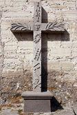 Cruz de pedra perto da parede — Fotografia Stock