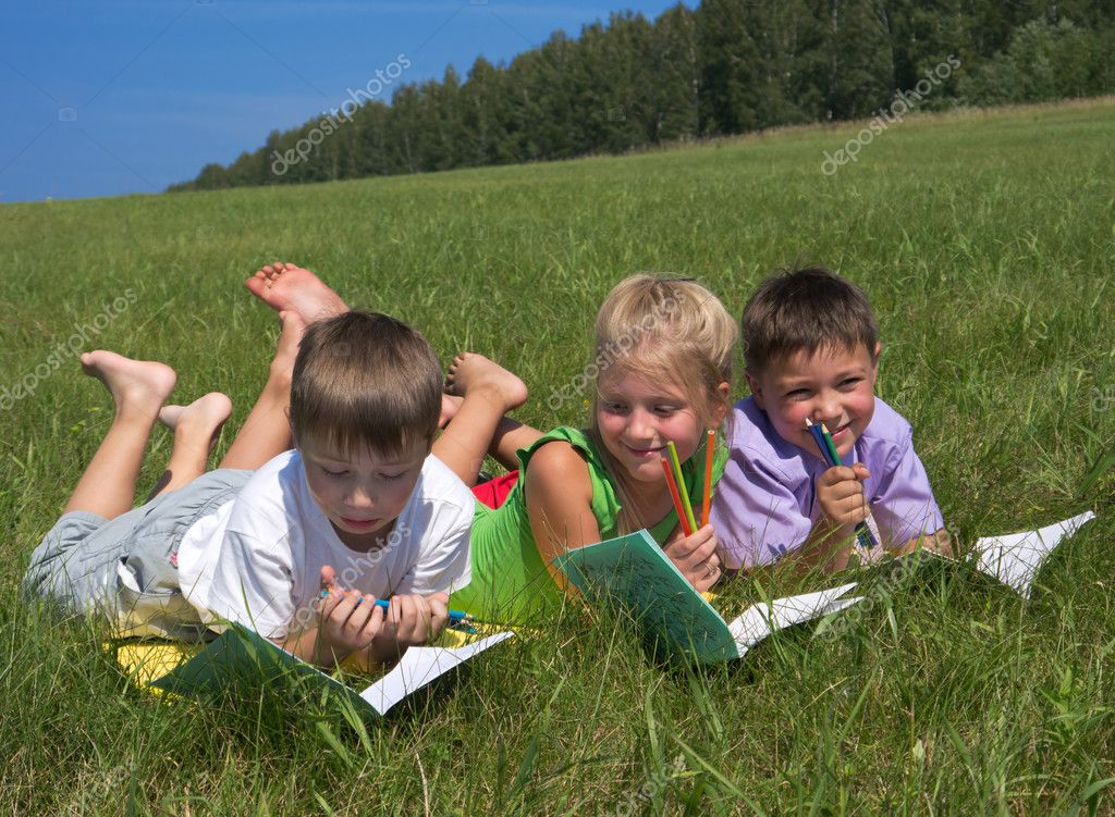 Three schoolkids at meadow writing in notebooks — Stock Photo #6465509