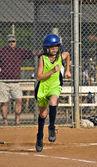 Jugador de softbol joven corriendo a primera base — Foto de Stock