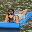 Foto Stock: Smiling WomFloating in Water