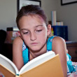 Stock Photo: Young Girl Reading Book in Her Room