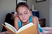 Young Girl Reading a Book in Her Room — Stok fotoğraf