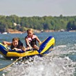Stock Photo: Boy and Girl Tubing Behind Boat