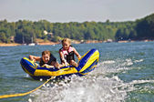 Boy and Girl Tubing Behind Boat — Stock Photo