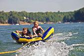 Boy and Girl Tubing Behind Boat — Stock Photo