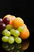 Tangerines, grapes, plumes and peaches at black background — Stock Photo