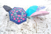 Multicolored umbrellas on snow — Stock Photo
