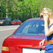 The girl the blonde speaks by phone about the broken red car in the summer — Stock Photo
