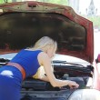 The girl the blonde repairs the car in a cowl in the summer, Moscow — Stock Photo