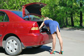 девушка блондинка ищет инструментов в багажник красный автомобиль — Стоковое фото