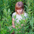Offended by a sad girl sitting and hiding in the tall grass in the summer — Stock Photo