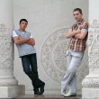 Two young men, surrounded by white columns — Stock Photo