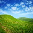 Green hills and blue sky with clouds — Stock Photo