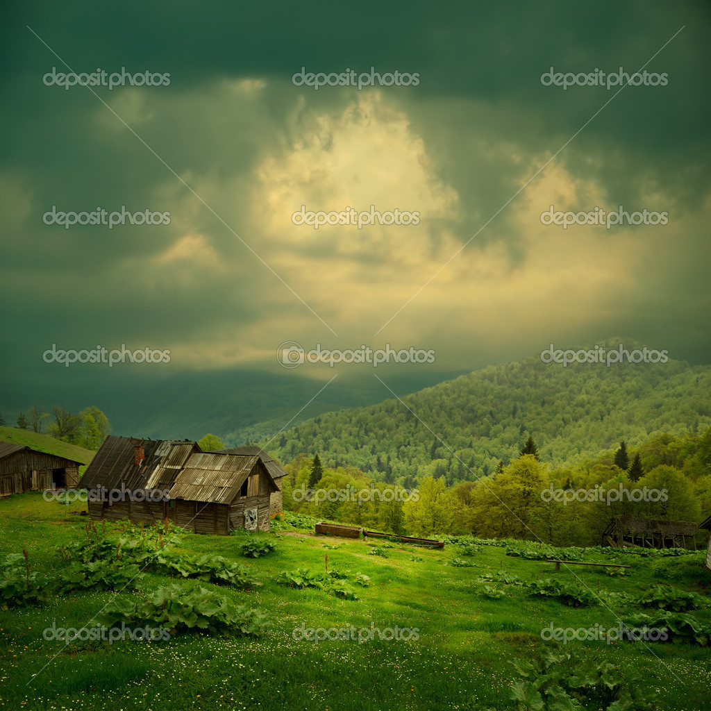 Mystery mountain landscape. Ray of light in dark clouds over the old wooden shack in green valley — Stock Photo #6217553