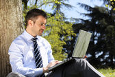 Man with computer in a park — Stock Photo
