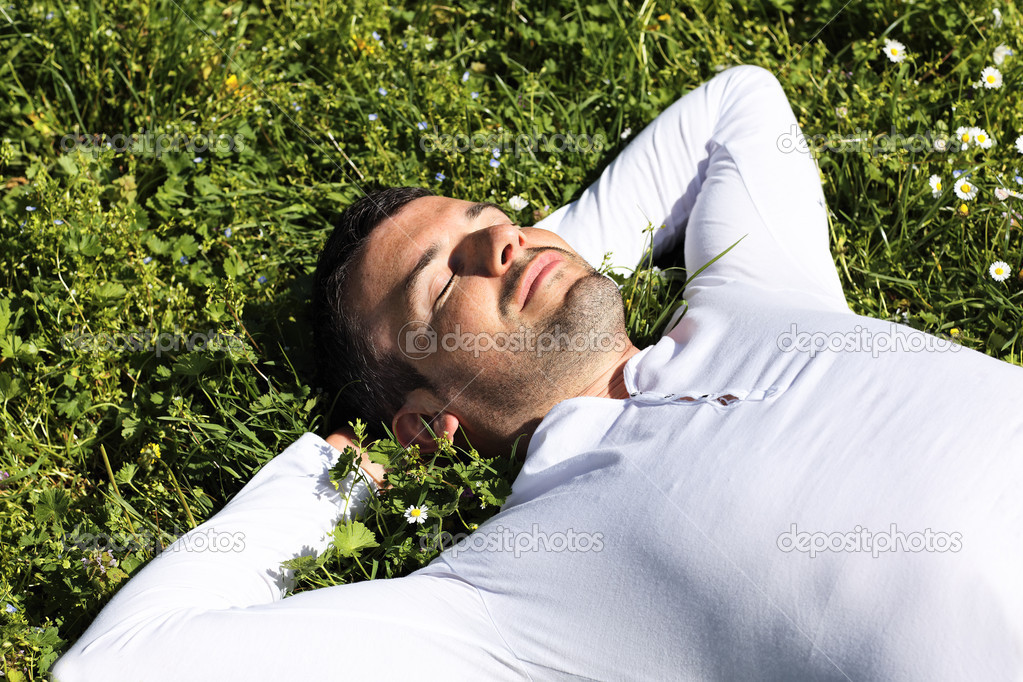Young man sleeping on the grass in a park — Stock Photo #5889879
