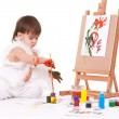 Cute baby painting with brush near easel — Stock Photo