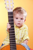 Child proposing play the guitar — Stock Photo