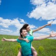 Happy young couple pointing out on summer field — Stock Photo
