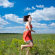 Happy young women running on summer field — Stock Photo