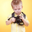 Little curious photographer watch photo on camera — Stock Photo #5807363