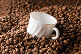 Empty coffee cup in beans — Stock Photo