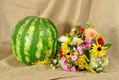The melon and autumn flowers against rough stuff — Stock Photo