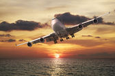Evening flight. Jet plane over the sea at sunset. — Stock Photo