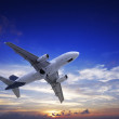 Stock Photo: Jet airplane in flight at sunset time