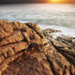 View of a rocky coast at sunset time. Long exposure vertical sho - Stock Photo