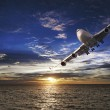 Jet plane over the sea at sunset time — Stock Photo #5895205