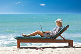 Young woman with laptop on the tropical beach — Stock Photo