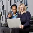 Business couple with notebook working outside — Stock Photo