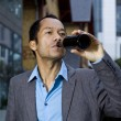 Smart casual business man drinking beer outdoors portrait in front of moder — Stock Photo