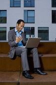 Smart business man working outdoors with laptop an wireless LAN — Stock Photo