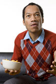 Man nibbling while watching television — Stock Photo