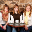 Three beautiful young students waiting drinking  coffee and havi - Stock Photo