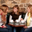 Three beautiful young students waiting drinking coffee and havi — Stock Photo #6082742