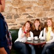 Man just arrived in a caffee where three girls were expecting hi — Stock Photo #6082783