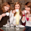 Three beautiful young students waiting drinking coffee and havi — Stock Photo #6086139