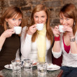 Three beautiful young students waiting drinking coffee and havi — Stock Photo