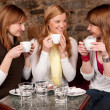 Three beautiful young students waiting drinking coffee and havi — Stock Photo #6086378