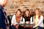 Man just arrived in a caffee where three girls were expecting hi — Stock Photo