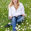 Beautiful young woman reading a book outdoors on a grass field i — Stock Photo #6093268