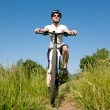 Stock Photo: Young girl riding a bike on a field path - offroad