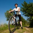 Young girl riding a bike on a field path - offroad — Stockfoto