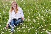 Piękna młoda kobieta, czytając książkę na zewnątrz na trawie pole i — Zdjęcie stockowe