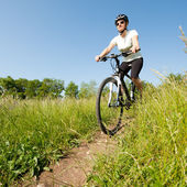 Young girl riding a bike on a field path - offroad — Stock Photo
