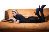 Smiling girl on sofa with laptop — Stock Photo