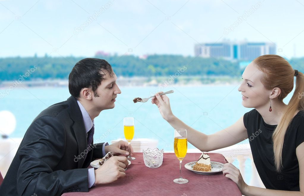 Date of young loving couple at restaurant on water or at yacht on tropical resort. They're looking at each other and smiling. — Stock Photo #6145378